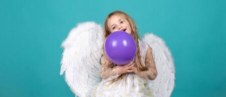 Wonderful blonde little girl in the image of an angel with white wings. Beautiful young girl wearing angel wings.