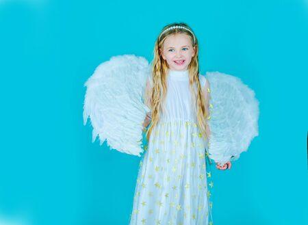 Hermosa joven con alas de ángel. Niño con vestido blanco largo y alas de ángel. Niña linda con alas blancas como Cupido.