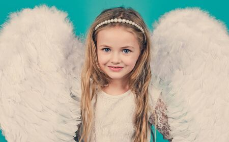 Wonderful blonde little girl in the image of an angel with white wings. Angel kid with blonde curly hair. Angel. Beautiful child angel posing and looking at camera. Foto de archivo