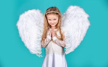 Niño con rostro angelical. Muchacha linda del niño que presenta con alas de ángel. Hermosa niña ángel de pie con los brazos cerca del pecho como en oración. Pequeñas manos de ángeles se cruzaron por ti.