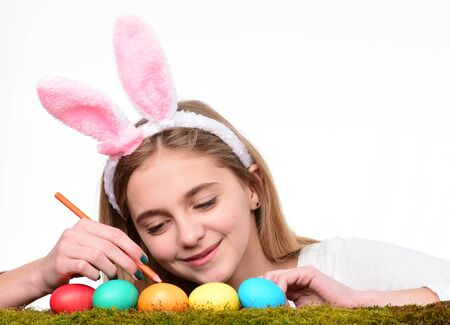 Traditional easter holidays decorations. Happy easter holidays concept. Cute smiling little girl wearing bunny ears and decorating colorful easter eggs. Stock Photo - 136805602
