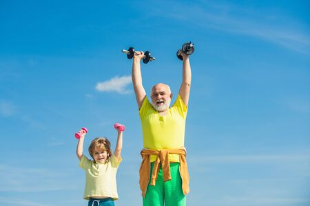 Active healthy life for family. Senior man and child exercising on blue sky. Grandfather and child in gym working out with weights. Healthy lifestyle. Stock Photo - 136805629