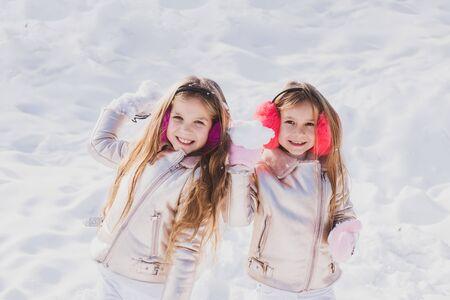 Retrato de niños de invierno. Retrato de dos niñas juegan con nieve en invierno. Niños de invierno posando y divirtiéndose. Foto de archivo