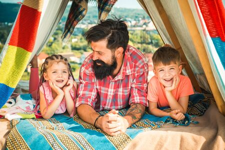 Father have fun with his cute daughter and son. Happy family enjoy being together and play. Young hipster bearded dad play with his children at colorful playhouse at the roof.