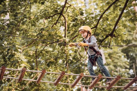 Balance beam and rope bridges. Go Ape Adventure. Child concept. Climber child on training. Portrait of a beautiful kid on a rope park among trees. Carefree childhood