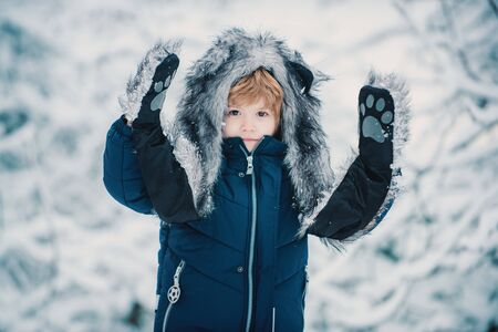 Merry Christmas and happy holidays. Winter kid posing and having fun. Concept winter Kids and nature. Funny kid coming to the winter forest on snow landscape. Stock Photo