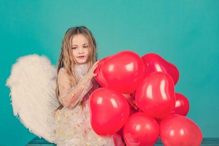 Día de San Valentín. Niña ángel feliz sobre blanco. Muchacha linda del niño que presenta con alas de ángel. Niño ángel. Hermoso angelito. Foto de archivo