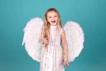 Looks like an angel. Happy angel girl over white. Christmas Cute little Angel. Beautiful little angel girl. Beautiful young girl wearing white wings.