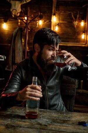 Man with beard holds glass brandy. Macho drinking. Degustation, tasting. Handsome bearded man. Do not drink and drive 版權商用圖片