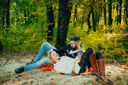 Autumn season concept. Young happy family having good time and smiling at autumn colorful park. Bearded man playing with blond hair of his wife. Sensual romantic photo.