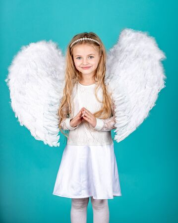 Cute child girl in white dress standing over color background. Child angel with a beautiful wings. Happy little Angel. Mischievous little angel girl standing with your clenched fists.