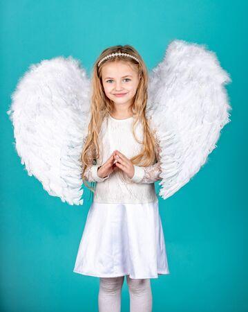Niña linda en vestido blanco sobre fondo de color. Niño ángel con hermosas alas. Angelito feliz. Niña ángel traviesa de pie con los puños cerrados.