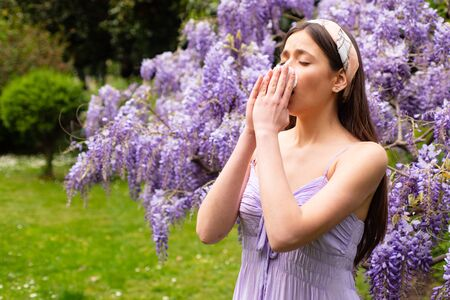 Sick woman sneezing covering nose with a wipe in a park. Young woman posing. Sick person. Spring allergy concept. Fashionable youth style. Allergic people. Among blooming trees and flowers in park.