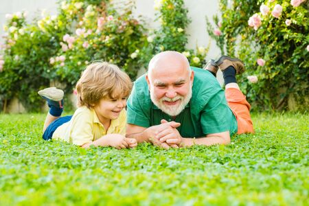 Zwei Generationen - Wochenende zusammen. Elternteil im Ruhestand. Älterer Mann mit Enkel im Park joggen. Familien tradition. Glücklicher Mann Familienkonzept lachen und Spaß zusammen haben. Standard-Bild
