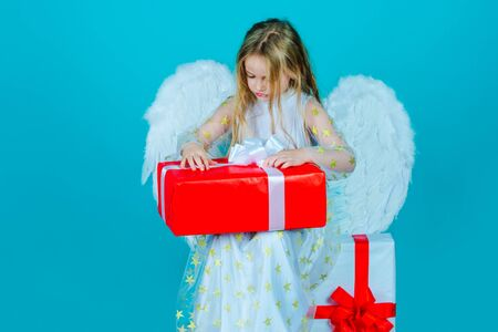 Valentines Day. Little angel girl open gift. Cute child girl posing with angel wings. Beautiful little angel. Angel child from heaven gives you gift.