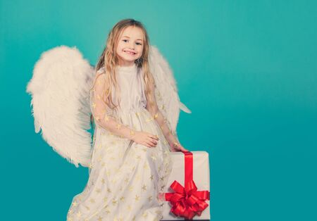 Valentines Day. Angel child from heaven gives you gift. Face of beautiful little angel girl on color background. Child angel with a beautiful wings. Looks like an angel. Фото со стока