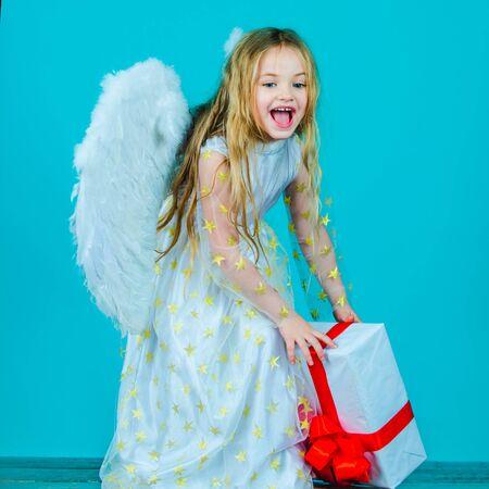Feliz día de San Valentín. El niño ángel del cielo te da un regalo. Navidad lindo angelito. Hermosa niña ángel. Hermosa joven con alas de ángel.