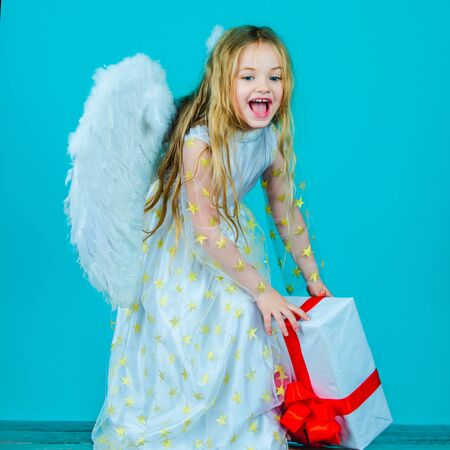 Happy Valentines Day. Angel child from heaven gives you gift. Christmas Cute little Angel. Beautiful little angel girl. Beautiful young girl wearing angel wings. Фото со стока