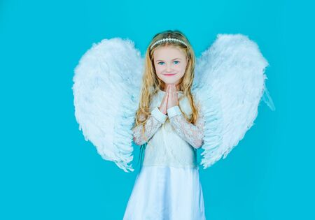 Face of beautiful little angel girl on color background. Looks like an angel. Angels little hands crossed for you. Mischievous little angel girl standing with your clenched fists.