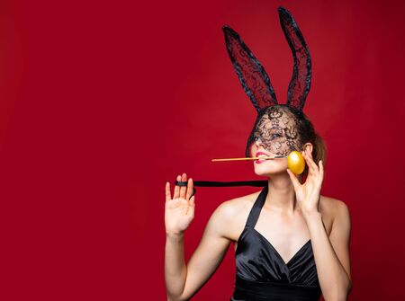 Sexy woman Easter bunny wearing mask and ears celebrating Easter holidays. Young sensual provocative female in bunny costume isolated at red background. Sexy bunny concept.