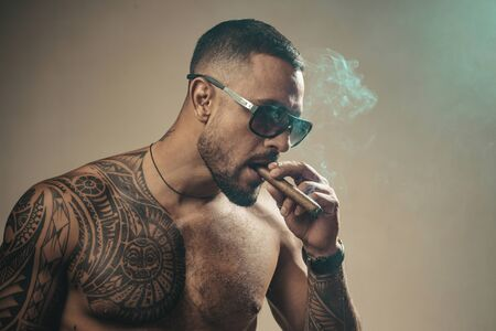 Attributes of men power, strength and luxury life. Strong confident tattooed man in luxury sunglasses smoking an elite cigar isolated at gray background. Bearded careless man smoke.