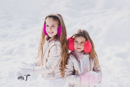 Winter clothing for baby and toddler. Happy winter time. Kids in snow. Two adorable young girls having fun together in beautiful winter park. Stock fotó