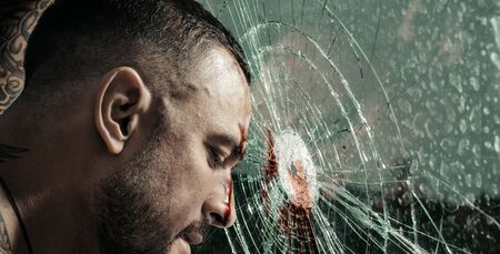 Destroy obstacles. Handsome brutal man near broken glass. Brutal handsome macho focused on fight result. Want to fight right now. Fight concept. Man muscular body punching. Concentrated on target 版權商用圖片
