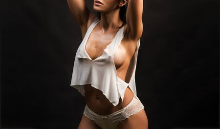 Beauty of womans body. Wet with water sensual young girl with slim fit figure and natural big bust. Attractive sexy woman wearing white underwear. Natural big boobs concept. 版權商用圖片