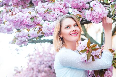 Beautiful woman with blooming Sakura tree and sunny day.
