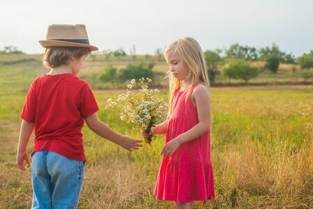 Childhood concept. Sweet angel children. Childhood on countryside. Valentines day. Love. Human emotions - kids first love. Happy children girl and boy hug on meadow in summer in nature.