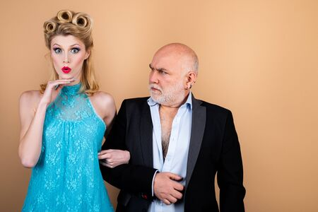 Difference of ages concept. Couple of younger woman and elder man isolated at orange background. Crafty blonde woman want to marry rich sugar daddy to get his money. Stock fotó