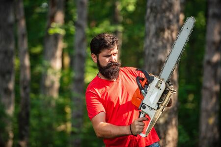 Lumberjack worker with chainsaw in the forest. Lumberjack in the woods with chainsaw axe. Lumberjack with chainsaw on forest background.