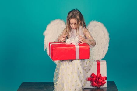Valentines Day. Angel child from heaven gives you gift. Cute child girl in white dress standing over color background. Child with angelic face. Valentines day. Saint Valentines Day card.