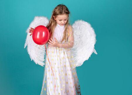 Día de San Valentín para niños. Cara de niña hermosa angelito sobre fondo de color. Niña bonita ángel. Niño con rostro angelical. Niño con vestido largo blanco y alas de ángel. Foto de archivo