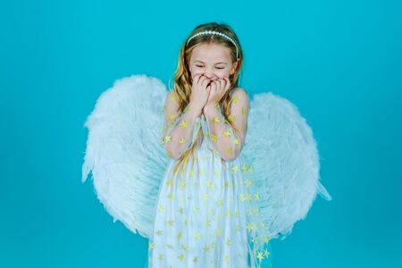 Valentines Day. Looks like an angel. Angel kid with blonde curly hair. Cute child girl in white dress standing over color background. Portrait of beautiful angel little girl with angels wings.