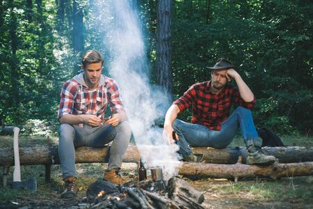 Company two male friends enjoy relaxing together in forest. Happy young people camping in woods. Friends sit on forest picnic. Group of two male backpackers relaxing near campfire.