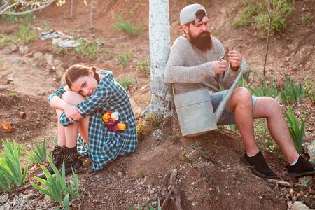 Eco farm. Summer farming. Image of two happy farmers with instruments. Farmars couple enjoy spring nature and take care about her plants. Reklamní fotografie