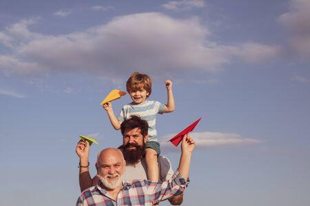 Szczęśliwy uśmiechający się chłopiec na ramieniu tata patrząc na kamery. Portret męski wielopokoleniowy. Chłopiec z ojcem i dziadkiem.