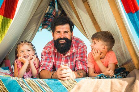 Młody brodaty tata hipster bawi się ze swoimi dziećmi w kolorowym domku na dachu. Ojciec bawi się ze swoją uroczą córką i synem. Szczęśliwa rodzina lubi być razem i bawić się. Zdjęcie Seryjne