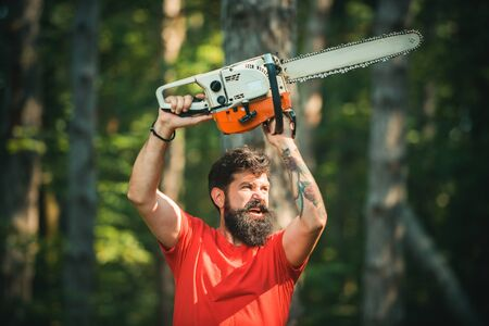 Lumberjack in the woods with chainsaw axe. Handsome young man with axe near forest. Chainsaw. Deforestation. Lumberjack worker with chainsaw in the forest.