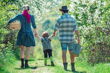 Happy family: mother, father, children son on spring garden background. Couple with son gardening in the backyard garden. Farming gardening and family concept