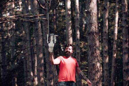 Lumberjack worker with chainsaw in the forest. Stylish young man posing like lumberjack. Lumberjack worker standing in the forest with chainsaw. Lumberjack holding the chainsaw.