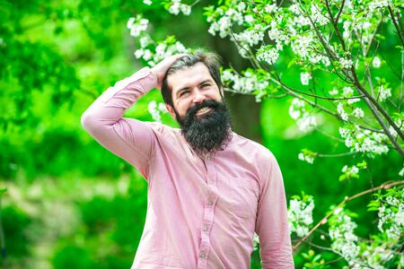 Portrait of bearded farmer. Handsome man spend time in the blossom orchard. Portrait of bearded man against blossom green spring field.