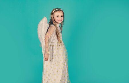 Niño con vestido largo blanco y alas de ángel. Angelito feliz. Tarjeta del día de San Valentín. Querubín. Hermosa niña ángel. Niña bonita ángel. Querubín.