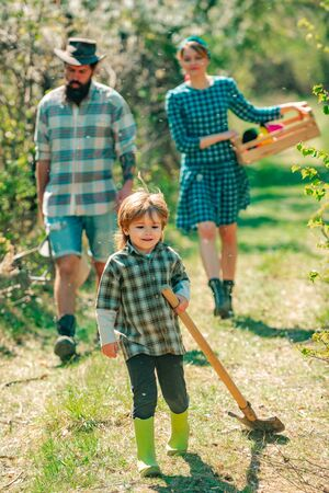 Family planting. Son helper. Family walking in agricultural field. Son help Family working on organic farm in spring. Portrait of a young happy family in yard during spring season.