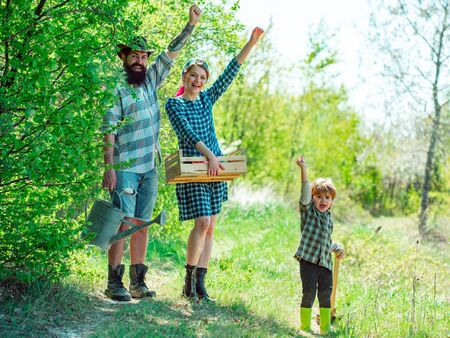 Happy family in garden. Farmars couple with son enjoy spring nature and take care about her plants. Earth day.