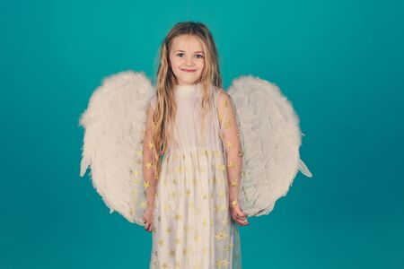 Valentines Day. Angel. Cute toddler girl in white wings as Cupid. Beautiful child angel posing and looking at camera. Фото со стока