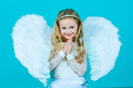 Valentines Day. Angel. Mischievous little angel girl standing with your clenched fists. Angels little hands crossed for you. Фото со стока