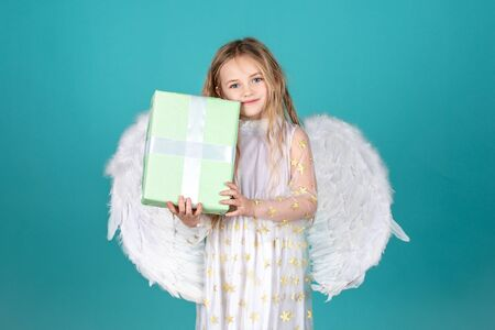 Valentines Day. Angel child from heaven gives you gift. Beautiful child angel posing and looking at camera. Cute child girl in white dress standing over color background. Child with angelic face.