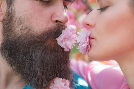 Kissing couple in spring nature close-up portrait. Passionate affectionate man and woman enjoying exciting moment of first kiss. Feeling desire.